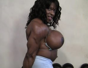 Female bodybuilder Yvette Bova trains her ebony muscles in the gym, first doing hack squats and posing nude to show off her massive legs, glutes and pecs, then working her big biceps and triceps. Then she starts playing with her big clit, while you watch in close-up. I just might let you suck on it, she says. Ready?