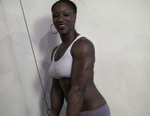 In the gym, Female Bodybuilder Mistress Empress is posing to show off her sexy legs, glutes and abs , and training her strong ebony muscles, working her biceps and triceps. She calls herself chiseled chocolate. You'll call her delicious.