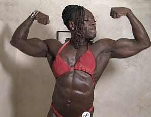Ebony muscle goddess Roxanne Edwards is a sight to behold. Sharply defined abs, bulging biceps and powerful glutes and quads are always on display when Roxanne shows up. An imposing site gets even more imposing when Roxanne puts on her red posing suit.
