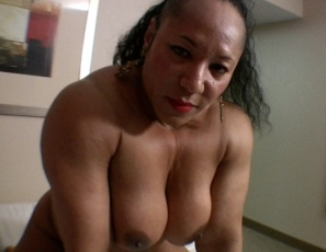 "Female bodybuilder Carmella Cureton poses nude for you in the bedroom, showing off her big ebony biceps, pecs, glutes, legs, calves and bare feet. Then she spreads her legs, showing you her pretty kitty, and rubs against a pillow to get off. ""Dirty, dirty, dirty,"" she says, because she knows that's the way you like it."
