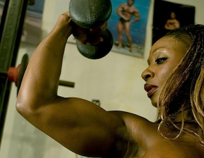 Bodybuilder Mae Kalamus, all in white, gets so excited while she does squats in the gym that she just has to pull her shorts aside. Then she takes them off entirely, showing her gleaming ebony glutes and legs, then squatting while nearly naked.