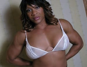 In the bedroom, ebony bodybuilder Kim Buck is taking off her pretty lacy panties and getting naked, posing to show you her tight glutes and powerful muscles, as well as her big clit and pretty pussy.