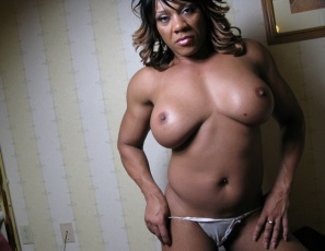 In the bedroom, professional bodybuilder Kim Buck is bringing sexy back, with a lot of looks at her powerful ebony glutes. She's posing, wearing sexy high-heeled sandals and tiny panties, then takes off the panties for you.