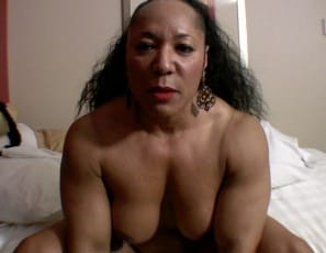 Bodybuilder Carmella Cureton is in the bedroom, masturbating her big ebony clit and wet pussy in close-up and scissoring a pillow with her muscular legs so hard that you'll wish it was you. You'll enjoy watching her sexy pecs, glutes and biceps as she gets herself off, saying, If you want to get something done right, you have to do it yourself.