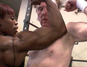 "Mistress Treasure gym domme's wimpy william in a video pose down, showing him the difference between ""soft"" and ""hard – rock hard,"" comparing her ebony double biceps with his and her hamstring with his ""no-string,"" then allowing him to touch her biceps, pecs, legs and glutes. ""Thank you, MT,"" he says, on his knees, and you will too."